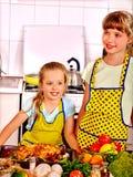 Niños que cocinan el pollo en la cocina Foto de archivo libre de regalías