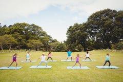 Niños que colocan y que hacen yoga Imagen de archivo