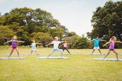Niños que colocan y que hacen yoga Imagenes de archivo