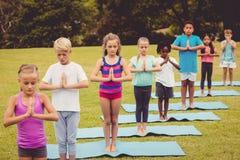 Niños que colocan y que hacen yoga Foto de archivo