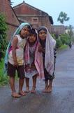 Niños que colocan y que se protegen contra la lluvia foto de archivo libre de regalías