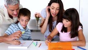 Niños que colorean con sus padres almacen de video