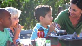 Niños que comen el almuerzo lleno al aire libre con el profesor almacen de metraje de vídeo