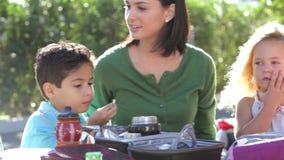 Niños que comen el almuerzo lleno al aire libre con el profesor metrajes