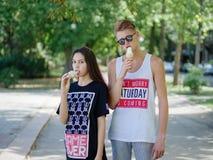 Niños que comen el helado Pares románticos una fecha en un fondo borroso del parque Concepto de la producción del helado Copie el Fotografía de archivo libre de regalías