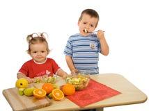 Niños que comen la ensalada de fruta foto de archivo libre de regalías