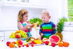 Niños que comen la fruta en una cocina blanca Fotos de archivo libres de regalías