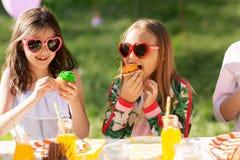 Niños que comen las magdalenas en fiesta de cumpleaños en el verano Imagen de archivo libre de regalías