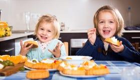 Niños que comen los pasteles sabrosos dentro imagen de archivo libre de regalías