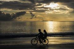 Niños que completan un ciclo en la playa en puesta del sol, Tailandia Fotografía de archivo libre de regalías