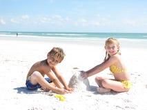 Niños que construyen castillos de arena Imagenes de archivo
