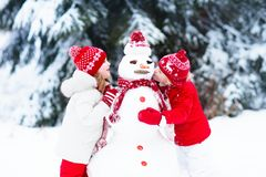 Niños que construyen el muñeco de nieve Niños en nieve Diversión del invierno Fotos de archivo libres de regalías
