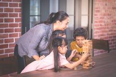 Niños que construyen la torre del bloque del juguete con el profesor fotografía de archivo