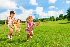6, 7 niños que corren con la red de la mariposa Imagen de archivo libre de regalías