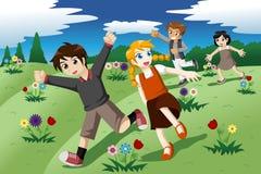 Niños que corren en el campo abierto de flores salvajes Fotografía de archivo libre de regalías
