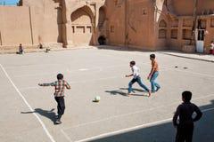 Niños que corren en patio del fútbol en la calle medio-oriental Imagenes de archivo