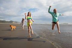 Niños que corren y que saltan en la playa Fotos de archivo