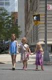 Niños que cruzan la calle en la señal del paseo Fotos de archivo