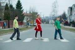 Niños que cruzan la calle en paso de peatones Imagenes de archivo