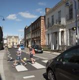 Niños que cruzan un camino ocupado Devizes Reino Unido Foto de archivo libre de regalías