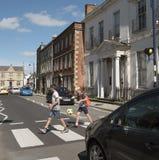 Niños que cruzan un camino ocupado Devizes Reino Unido Fotos de archivo libres de regalías
