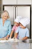 Niños que cuecen las galletas con la abuela Foto de archivo