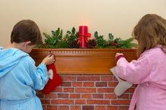 Niños que cuelgan medias sobre la chimenea Imágenes de archivo libres de regalías