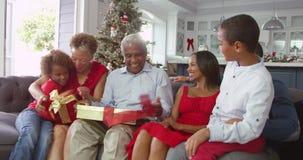 Niños que dan a abuelos los regalos de la Navidad en casa - sacuden los paquetes e intento para conjeturar cuál está dentro