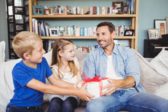 Niños que dan la caja de regalo para engendrar mientras que se sienta en el sofá imagenes de archivo