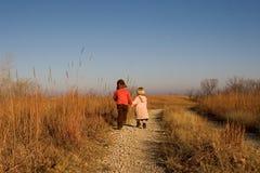 Niños que dan un paseo abajo del camino Foto de archivo libre de regalías