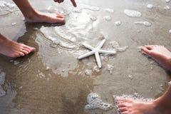 Niños que descubren estrellas de mar en la playa Fotos de archivo