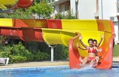 Niños que deslizan abajo una diapositiva de agua Fotos de archivo libres de regalías