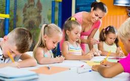 Niños que dibujan así como profesor particular en el grupo de la afición Foto de archivo libre de regalías