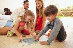 Niños que dibujan con sus padres en sala de estar Foto de archivo libre de regalías