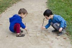 Niños que dibujan dentro de la arena Fotografía de archivo