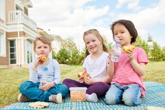 Niños que disfrutan de comida campestre en césped Foto de archivo libre de regalías