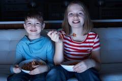 Niños que disfrutan de la comida mientras que ve la TV Imagenes de archivo