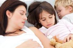 Niños que duermen con su madre Imágenes de archivo libres de regalías