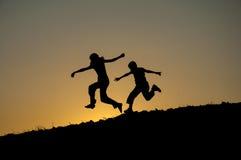 Niños que ejecutan la silueta Fotografía de archivo