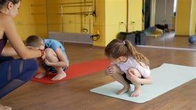 Niños que ejercitan debajo del instructor Supervision almacen de video