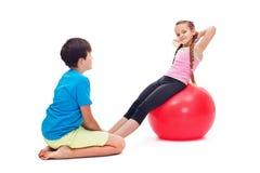 Niños que ejercitan junto usando una bola de goma gimnástica grande Fotos de archivo