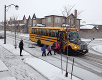 Niños que entran en el autobús escolar después de una noche nevosa Imágenes de archivo libres de regalías