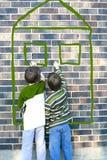 Niños que escriben en la pared de ladrillo Fotos de archivo