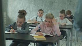 Niños que escriben notas en clase durante la lección metrajes