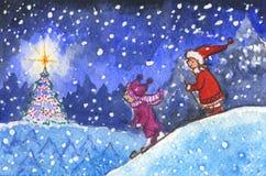 Niños que esquían en noche de Navidad imagenes de archivo