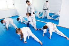 Niños que estiran antes de clase del karate Imagen de archivo