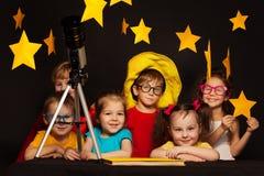 Niños que estudian astronomía con el telescopio imágenes de archivo libres de regalías