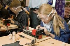 Niños que estudian la máquina de la carpintería Imágenes de archivo libres de regalías
