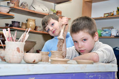 Niños que forman la arcilla en estudio de la cerámica Imágenes de archivo libres de regalías