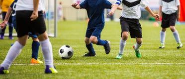 Niños que golpean el partido de fútbol con el pie Muchachos que juegan al juego de torneo del fútbol en echada Fotos de archivo